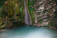 Rustige die rotsen met klimop en mos met waterval worden behandeld die neer stromen stock foto's