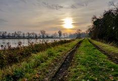 Rustige die scène van de de winterzon tijdens schemer, met een overstroomd moerasland in de voorgrond wordt gezien stock foto