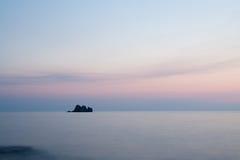Rustige mening met rots bij zonsondergang Stock Afbeelding