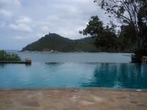 Rustige oneindigheidspool in Thailand die berg en oceaanhorizon overzien stock afbeelding