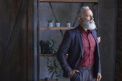 Rustige ongeschoren oude zakenman die in flat situeren royalty-vrije stock foto's