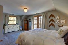 Rustige slaapkamer met geheld plafond en deuren aan aardig dek Stock Afbeeldingen