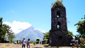 Rustige toneelmening van Mayon-vulkaan achter de beroemde die ruïnes van Cagsawa-kerktoren door vulkanische lavaeeuwen wordt begr stock videobeelden