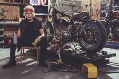 Rustige vrouwelijk trekt oppoetsende motorfiets terug stock afbeelding