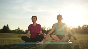 Rustige vrouwen die in halve lotusbloem bij zonsondergang mediteren stock footage