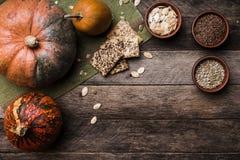 Rustikale Artkürbise mit Samen und Plätzchen auf Holztisch Stockfotos