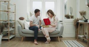 Rustikale Atmosphäre zu Hause für ein junges Paar, junger Mann, der ein großes Geschenk für seine Frau, sie etwas feiernd gibt stock video footage