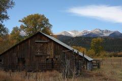 Rustikale Colorado-Scheune mit Bergen im hinteren Boden Lizenzfreie Stockfotos