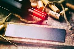 Rustikale Einstellung mit Rotweinflasche und -korken stockbild