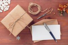 Rustikale Geschenkbox und Umschlag mit leerem Papier verzierten Werkzeuge und Feiertagszubehör auf Holztisch Lizenzfreie Stockfotografie