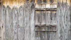 Rustikale hölzerne Scheunenwand mit Fensterladenhintergrund Stockfoto