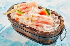 Rustikale hölzerne Wanne mit frischem Wassermeloneneis am stiel Lizenzfreie Stockbilder