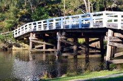 Rustikale Holzbrücke über Fluss im Wald Stockfoto