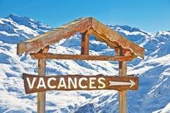 Rustikale Holzschild vacances, schneebedeckter Gebirgshintergrund Stockfotografie