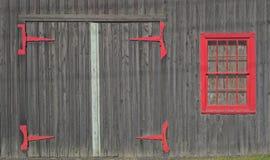 Rustikale Holztür mit roten Scharnieren und rotem gestaltetem Fenster stockfotos