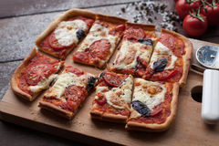Rustikale italienische Pizza mit Mozzarella-, Käse- und Basilikumblättern Lizenzfreies Stockfoto