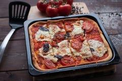 Rustikale italienische Pizza mit Mozzarella-, Käse- und Basilikumblättern stockfoto