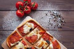 Rustikale italienische Pizza mit Mozzarella-, Käse- und Basilikumblättern stockfotografie