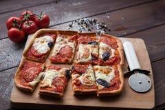 Rustikale italienische Pizza mit Mozzarella-, Käse- und Basilikumblättern stockfotos