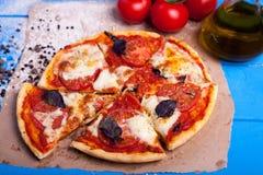 Rustikale italienische Pizza mit Mozzarella-, Käse- und Basilikumblättern lizenzfreie stockfotografie