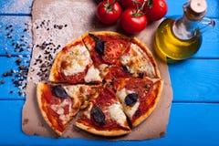 Rustikale italienische Pizza mit Mozzarella-, Käse- und Basilikumblättern Stockbild