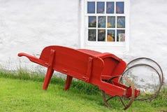 Rustikale rote Schubkarre durch Fenster Stockfoto