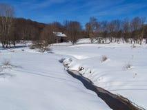 Rustikale Scheune über Snowy-Feld mit Nebenfluss und Bergen Stockfoto