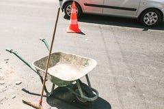 Rustikale schmutzige Bauschubkarre mit Stoßbesen auf der Straße, orange Straßenbaukegel im Hintergrund Stockfoto