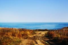 Rustikale Straße zur Küste Das Panorama von einem blauen Meer stockbild