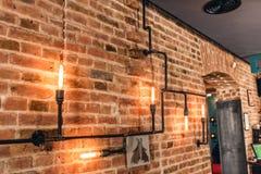 Rustikale Wände des Restaurants, Innenarchitekturlampen der Weinlese, Metallrohre und Glühlampen Stockfotografie