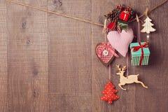 Rustikale Weihnachtsdekorationen, die über hölzernem Hintergrund mit Kopienraum hängen Lizenzfreie Stockfotos