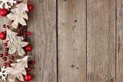 Rustikale Weihnachtsseitengrenze mit hölzernen Verzierungen und Beeren auf gealtertem Holz Stockfotos