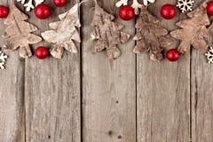 Rustikale Weihnachtsspitzengrenze mit hölzernen Verzierungen und rotem Flitter auf gealtertem Holz Lizenzfreie Stockbilder