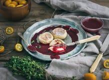 Rustikaler Frühstückssatz Russischer Käse backt auf einer Weinlesemetallplatte mit Lingonberrystau, frische japanische Orangen, T Lizenzfreies Stockfoto