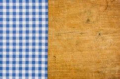 Rustikaler hölzerner Hintergrund mit einer blauen karierten Tischdecke stockbild