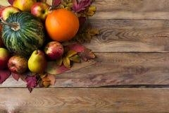Rustikaler Hintergrund der Danksagung mit grünem Kürbis, orange Zwiebelkürbis, Fallblättern, Äpfeln und Birnen auf dem Holztisch, stockfotos