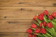 Rustikaler Hintergrund mit roten Tulpen lizenzfreie stockfotografie
