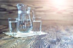 Rustikaler Hintergrund Weinlesetabelle und Gläser Wasser Lizenzfreies Stockfoto