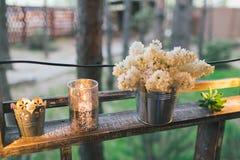 Rustikaler Hochzeitsdekor, belichteter Regalstand mit Flieder und suc Stockfotografie