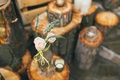 Rustikaler Hochzeitsdekor, verzierte Flasche mit stieg auf den Stumpf lizenzfreie stockfotos