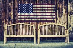 Rustikaler Klotz setzt mit Retro- USA-Flagge - auf die Bank Lizenzfreies Stockfoto