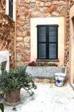 Rustikaler Mittelmeerpatio mit Blumentöpfen und Fensterläden Stockfoto