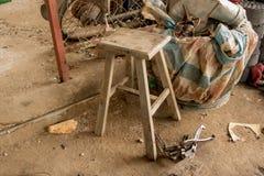 Rustikaler Schemel-Stuhl in der unordentlichen Garage - Weinlese-Haus lizenzfreies stockfoto