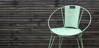 Rustikaler Stuhl im Freien gegen Zaunhintergrund lizenzfreie stockfotografie