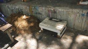 Rustikaler weißer Schemel-Stuhl mit Stapel des Stroh-Heuschobers nahe bei schmutziger gemalter Wand stockfoto