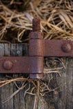 Rustikales altes Metallabhängung vom verwitterten Scheunenholz, das auf dem Gebiet legt stockbild