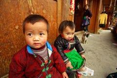 Rustikales asiatisches Kind 3 Jahre alt, sitzendes Hofholzhaus. Stockbilder