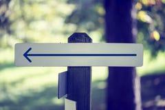 Rustikales bewaldetes Schild mit einem linken Pfeil Stockbilder