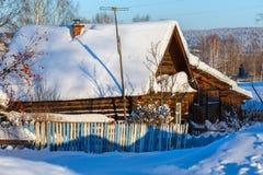 Rustikales Blockhaus bedeckt mit Schnee Dorf Visim, Swerdlowsk-Region, Russland Lizenzfreies Stockfoto