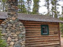 Rustikales Blockhaus des Steinkamins im Nationalpark Stockbilder